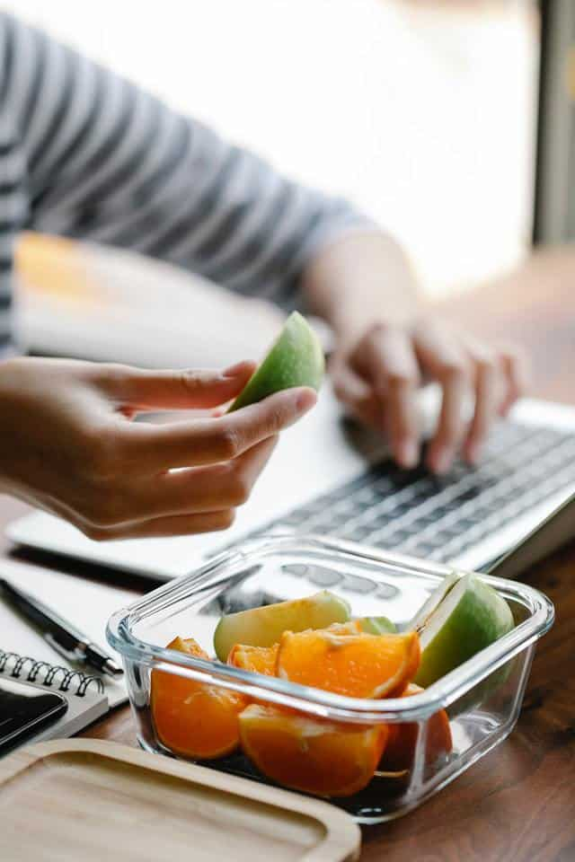 Person working at computer with meal prep container holding fruit